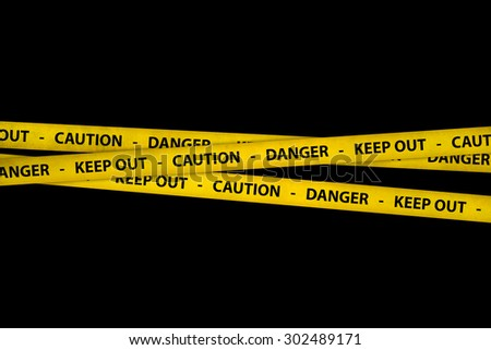 Yellow caution tape strips with text of keep out, danger and caution, on black background. - stock photo