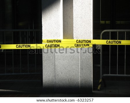 Yellow caution tape wrapped around a concrete pillar - stock photo