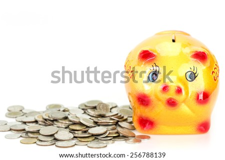 Yellow ceramic piggy bank and coin isolated on white background - stock photo