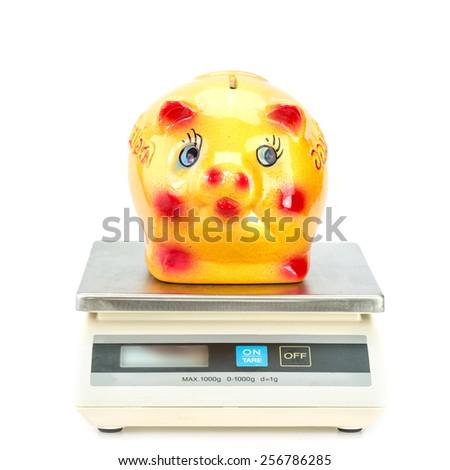 Yellow ceramic piggy bank on digital scale - stock photo
