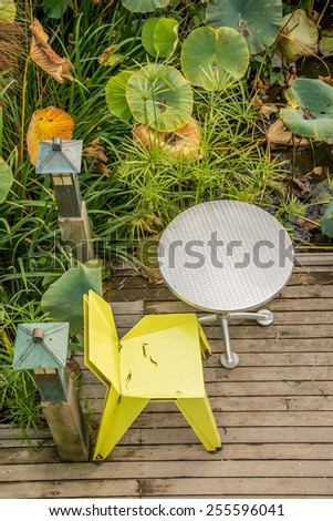Yellow chair and aluminum table on wood deck surrounded with green plants - stock photo