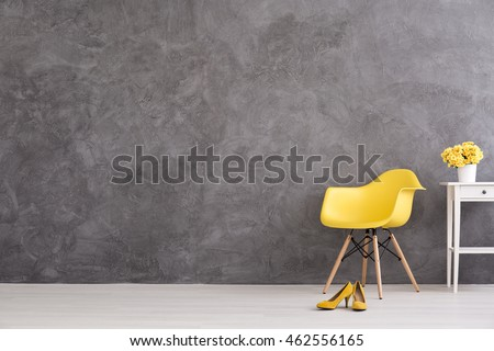 Yellow Chair, Shoes And Flower On The Table On A Background Of A Gray  Concrete