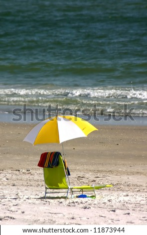 Yellow chair with beach towel on Florida Gulf Coast. - stock photo