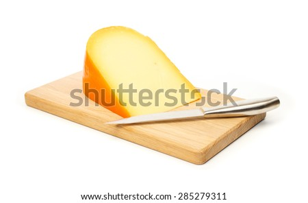 Yellow cheese and kitchen knife on a cutting board against white background - stock photo