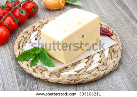 Yellow cheese brick with mint leaves on the wood background