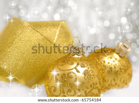 Yellow christmas balls and ribbon over blurry background. Shallow depth of field