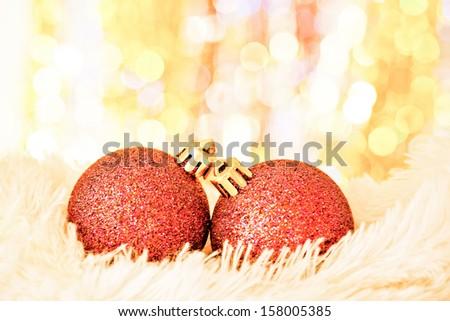 yellow christmas balls on white fur and  colorful lights  - stock photo