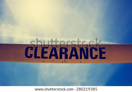 yellow clearance sign with view of cloudy sky with a retro instagram filter (shallow depth of field) - stock photo