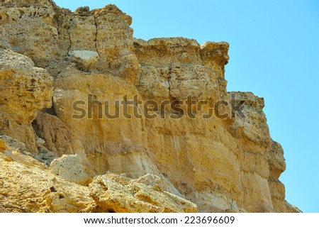 yellow cliff against blue sky - stock photo