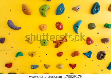 Yellow climbing wall with colorful rocks - stock photo