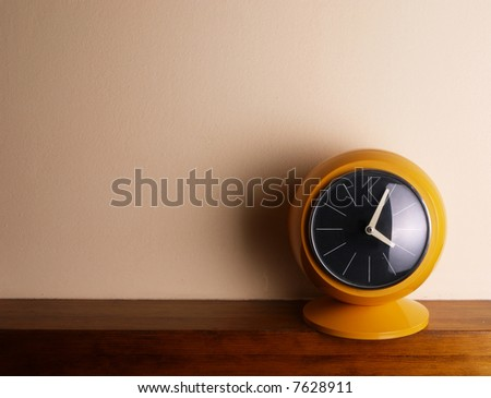 yellow clock on the shelf - stock photo