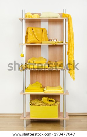Yellow clothes nicely arranged on a shelf. Tidy wardrobe with color coordinated clothes and accessories.