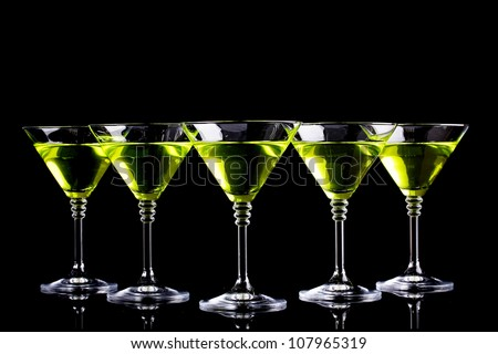 Yellow cocktail in martini glasses isolated on black - stock photo