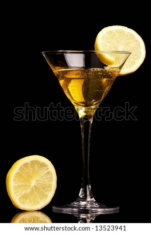 Yellow cocktail  with lemon on black background - stock photo