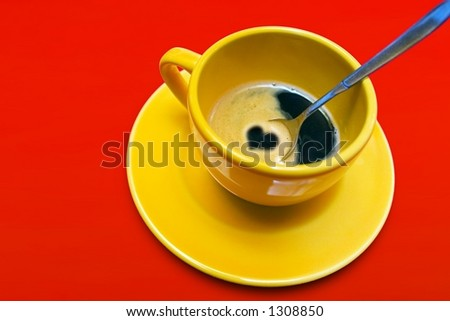 Yellow coffee cup with heart on a red background - stock photo