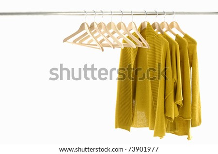Yellow colors clothes and wood coat hanger on hangers at the show - stock photo