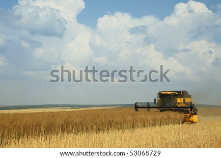 Yellow combine harvester on blue sky - stock photo