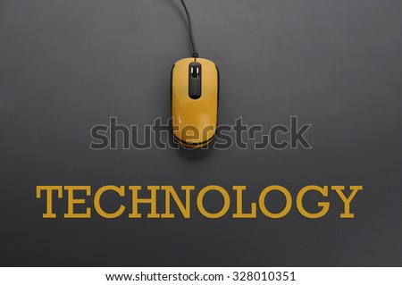 Yellow computer mouse and word Technology - education concept. Low light - stock photo