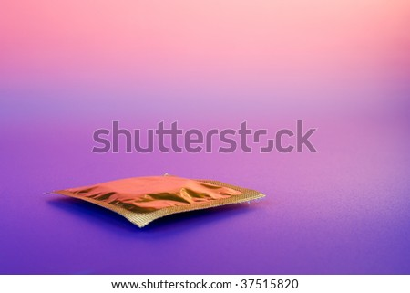 Yellow condom on color background - stock photo
