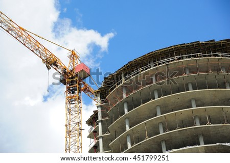 Yellow construction crane and unfinished building - stock photo
