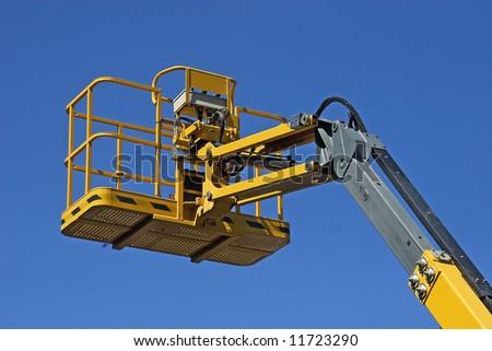 Yellow construction crane basket against blue sky. - stock photo