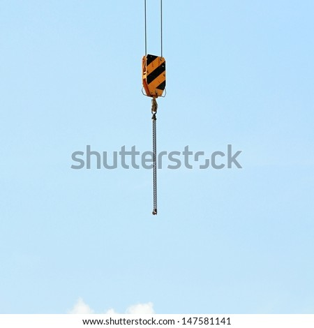 Yellow construction crane hook on a clean blue sky background - stock photo