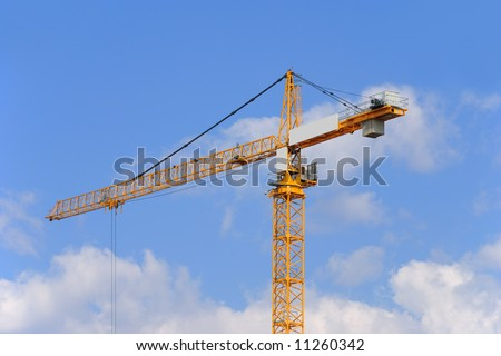 Yellow construction crane on a sky background - stock photo