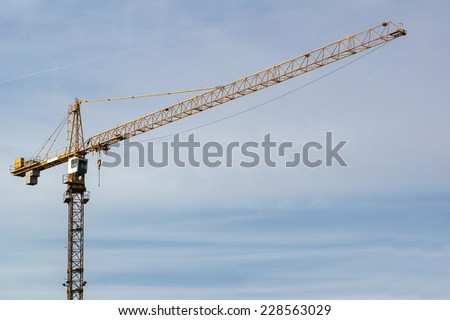 Yellow construction crane with blue sky background - stock photo