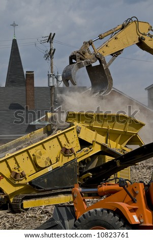 Yellow construction equipment loading rubble into a dump truck with an orange bulldozer in the foreground