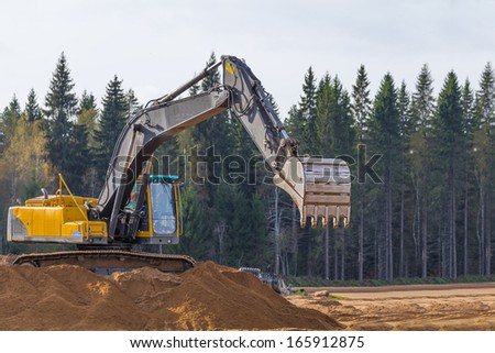 Yellow Construction Excavator at Work - stock photo