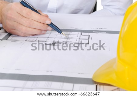 yellow construction helmet on the table builder - stock photo