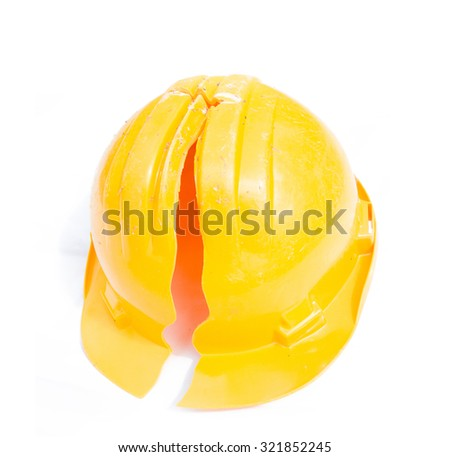 Yellow construction helmet with a large crack isolated. A trace of an accident at work. Life insurance - stock photo