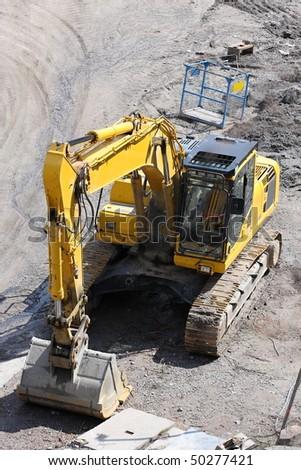 Yellow construction machinery - digger - stock photo