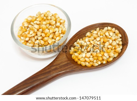 yellow corn grain and spoon isolated on white background - stock photo