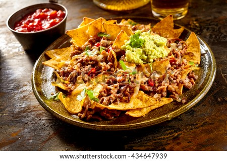 Yellow corn nacho chips garnished with ground beef, guacamole, melted cheese, peppers and cilantro leaves in plate on wooden table - stock photo