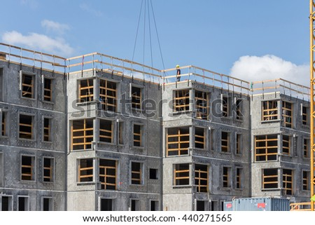 Yellow crane and building construction site against blue sky. Grey High-rise building under construction in a new residential area of Copenhagen, Denmark. Future residential building. Big windows. - stock photo