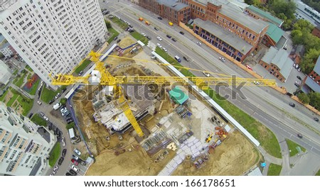 Yellow crane at construction site near residential complex. View from unmanned quadrocopter. - stock photo