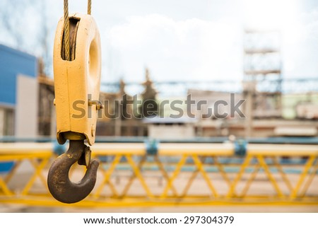 Yellow crane hook with some industrial buildings on the background - stock photo