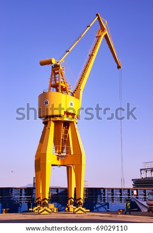 Yellow crane unloading cargo ships in the dock - stock photo