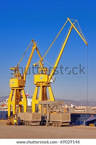 Yellow Cranes unloading a cargo ship on the dock - stock photo