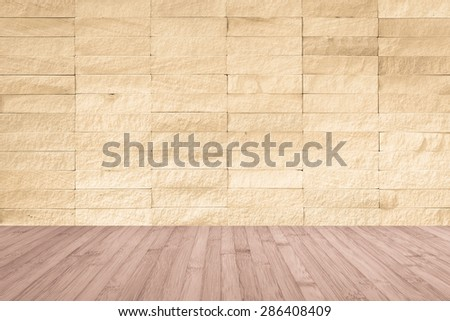 Yellow cream brown rock tile wall with wooden floor in light red brown color tone for interior background     - stock photo