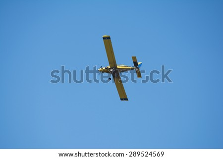 Yellow crop-duster airplane turning around in flight to fly back over the field and spray the next sector of the crop.  Blue sky background.  The Mississippi agricultural industry. - stock photo