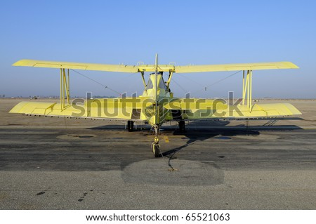 Yellow crop duster biplane with spray nozzles mounted on wing trailing edge - stock photo