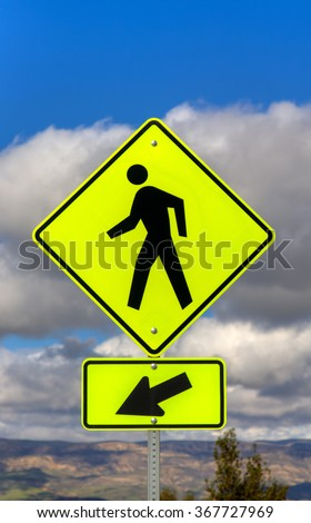 Yellow crosswalk sign with human icon and arrow pointing left. - stock photo