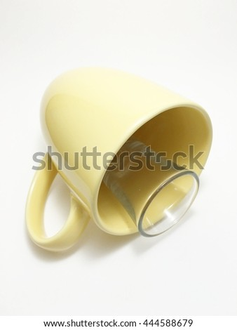 yellow cup and small clear cup  is falling - stock photo