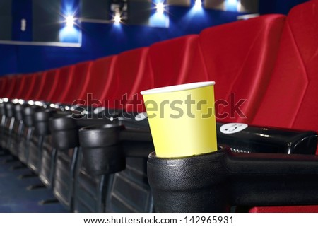 Yellow cup for popcorn is stand at red seat in auditorium in cinema theater. - stock photo