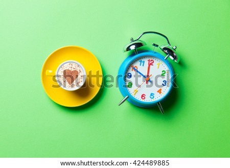 yellow cup of coffee and blue clock on the green background