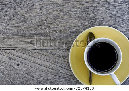 Yellow cup of coffer over the old wood - stock photo