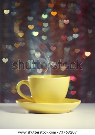 Yellow cup of tea in the background bokeh in the form of hearts. Illustration on the Valentine's Day. - stock photo