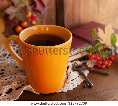 Yellow cup of tea, notebook, old key and autumn leaves on a wooden table, autumn time. Selective focus - stock photo